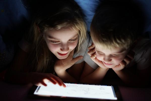 Siblings on tablet at night time